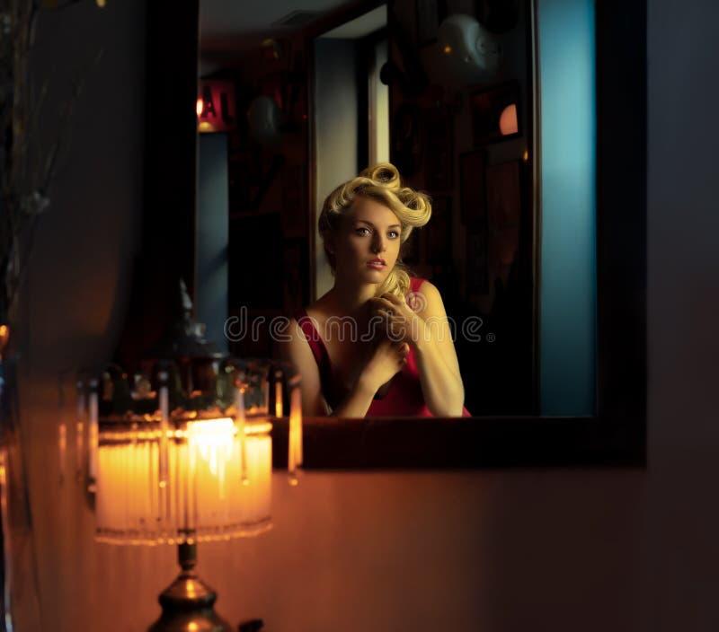 Härlig blondin som ser henne i en spegel arkivfoton