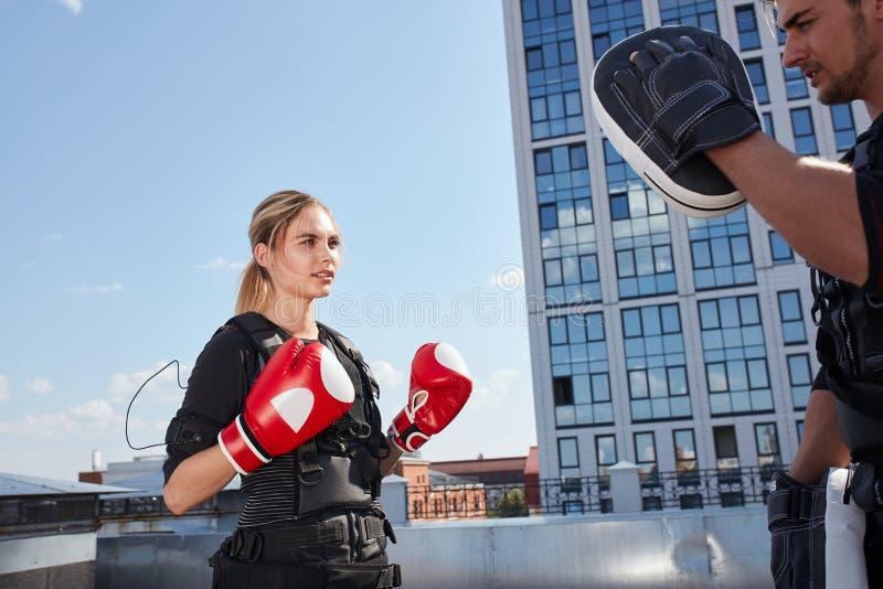 Härlig blondin som utarbetar med boxninghandskar och ems-dräkten arkivfoton