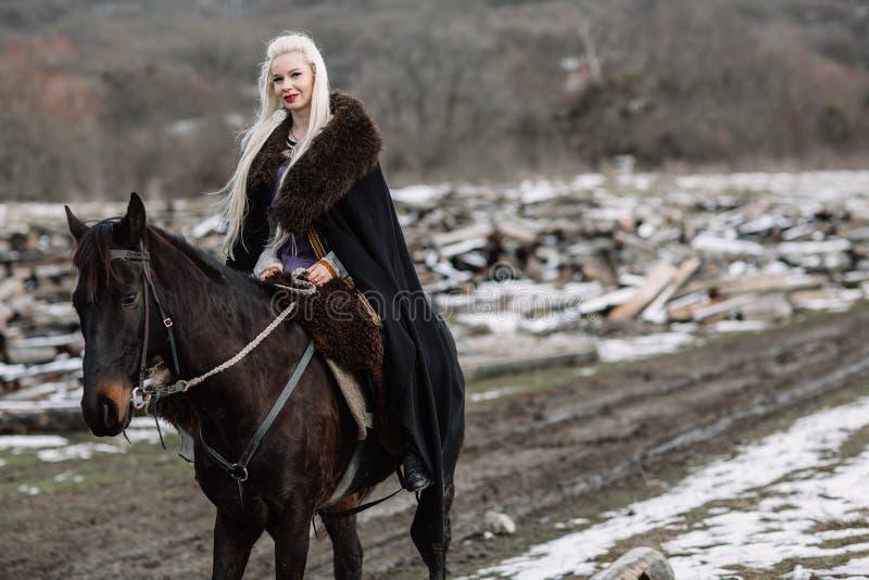 Härlig blondin Viking i en svart udde på hästrygg royaltyfria foton