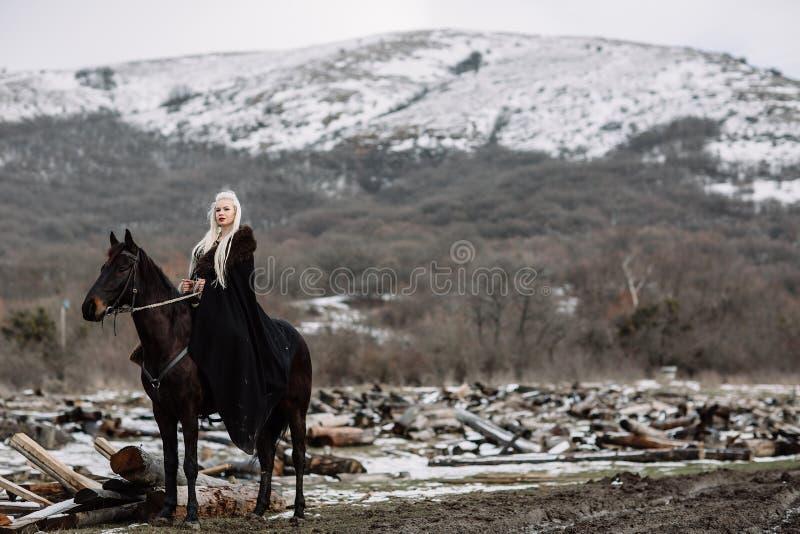 Härlig blondin Viking i en svart udde på hästrygg fotografering för bildbyråer