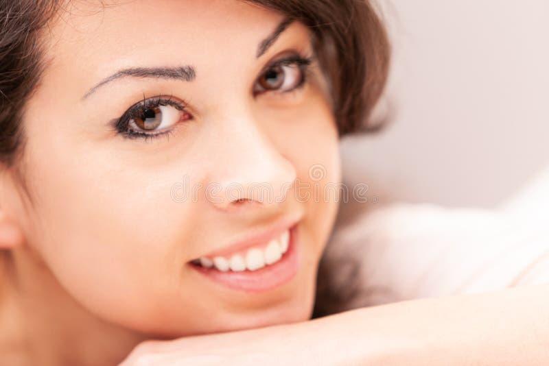 Härlig blyg kvinna som ler på hennes soffa arkivfoto