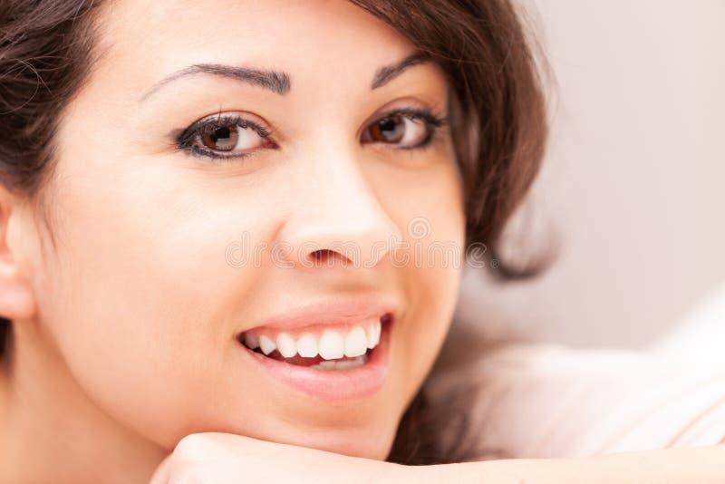 Härlig blyg kvinna som ler på hennes soffa royaltyfria foton