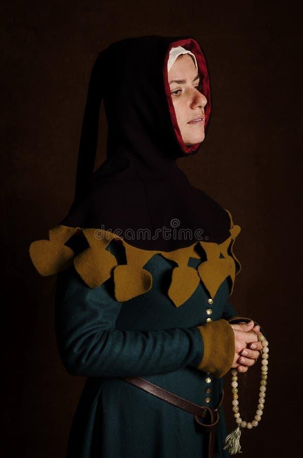 Härlig blygsam flicka i en medeltida klänning med en huv arkivfoton