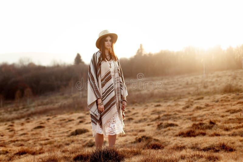 Härlig bohokvinnahipster som tycker om solnedgång och poserar på sol l arkivbild