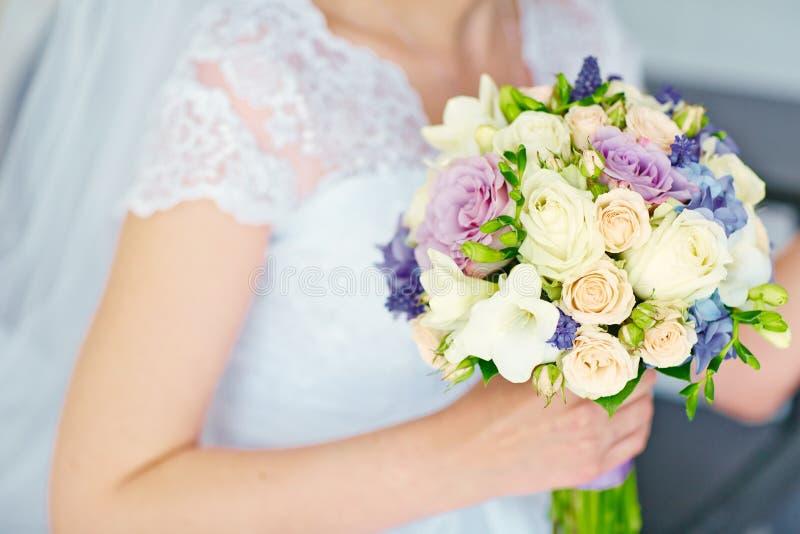Härlig bröllopbukett av blommor i händer av bruden royaltyfria bilder