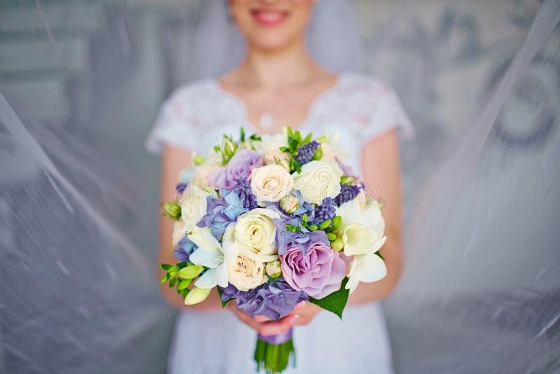 Härlig bröllopbukett av blommor i händer av bruden royaltyfri bild