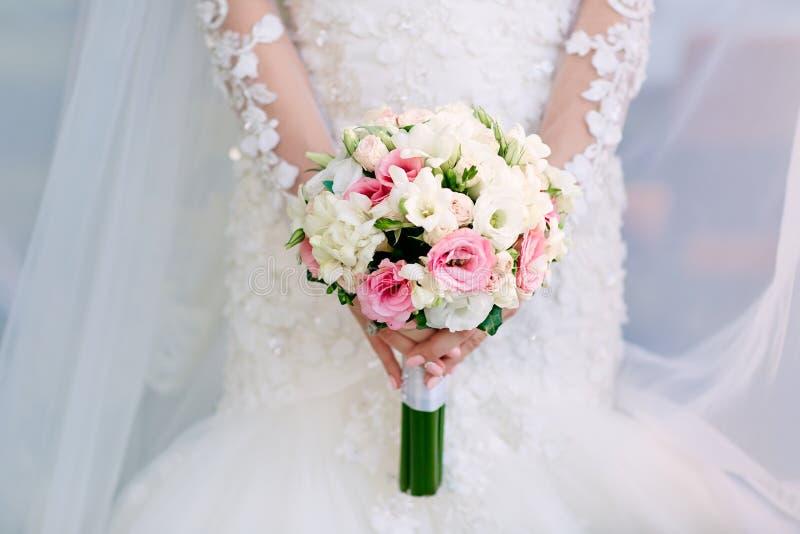 Härlig bröllopbukett av blommor i händer av bruden fotografering för bildbyråer