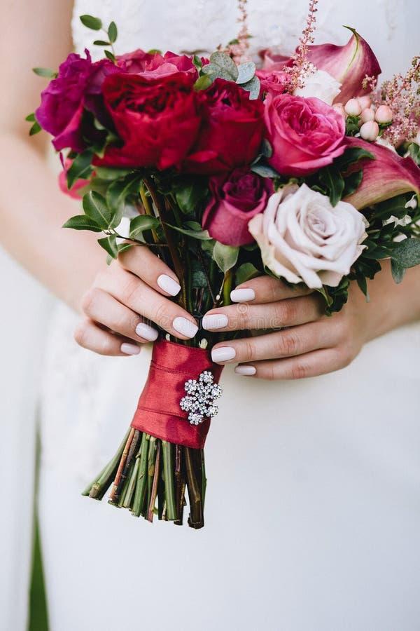 Härlig bröllopbukett av fuchsian av rosor i händerna av bruden med en härlig manikyr vertikalt fotografering för bildbyråer