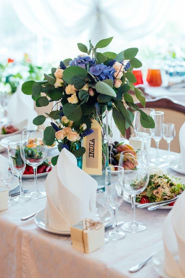 Härlig bröllopbukett av kräm- rosor, blåttblommor och eukalyptuns på matställetabellen royaltyfri foto