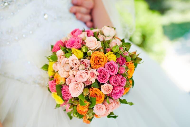 Härlig bröllopbukett av rosor i händer av bruden arkivbilder
