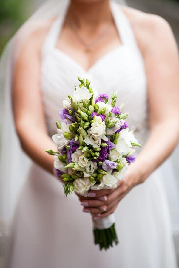 Härlig bröllopbukett i händer av bruden royaltyfri bild