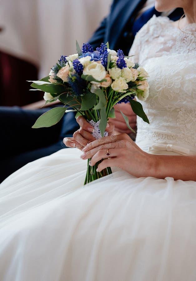Härlig bröllopbukett i händer för brud` s Brud med weddbuketten arkivfoto