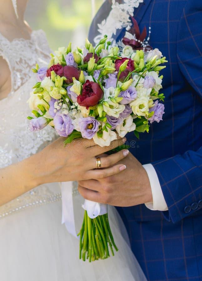 Härlig bröllopbukett i händerna av bruden royaltyfri fotografi