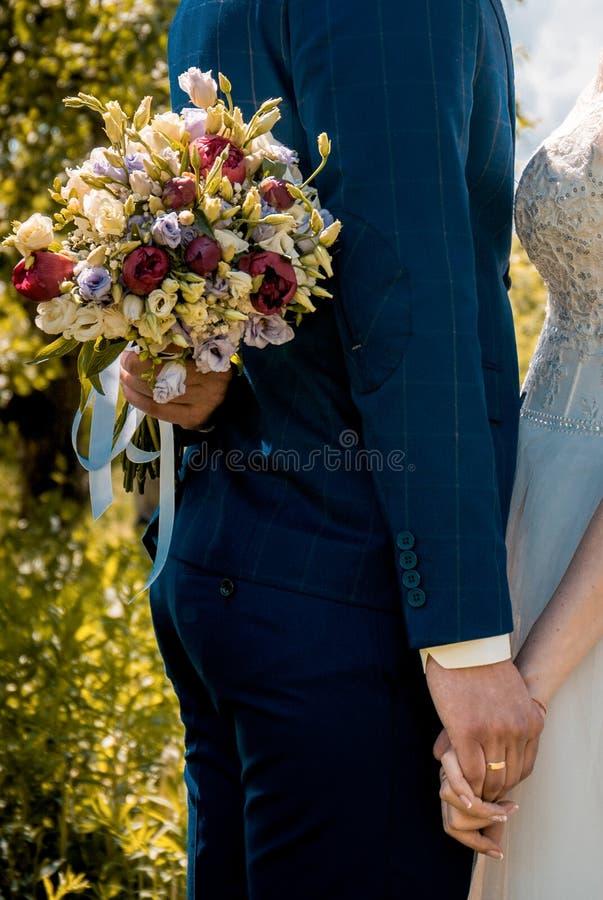 Härlig bröllopbukett i händerna av bruden royaltyfri foto