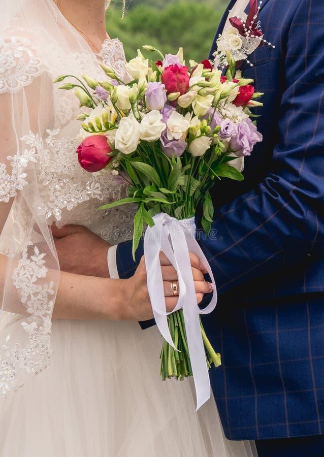 Härlig bröllopbukett i händerna av bruden royaltyfria foton