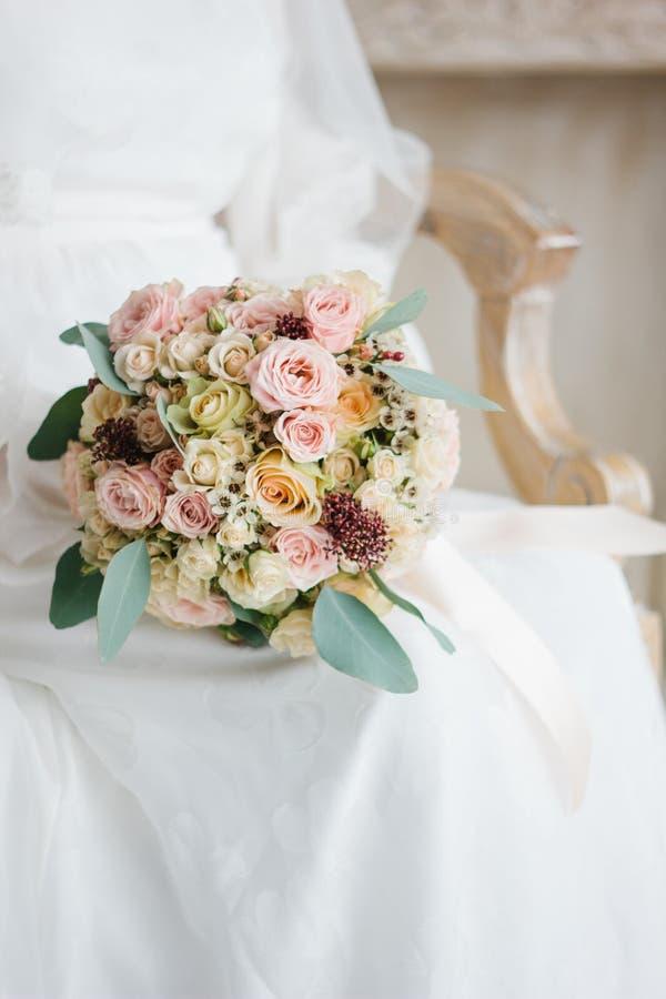 Härlig bröllopplats - brudsammanträde i stol- och innehavbröllopbukett arkivbild