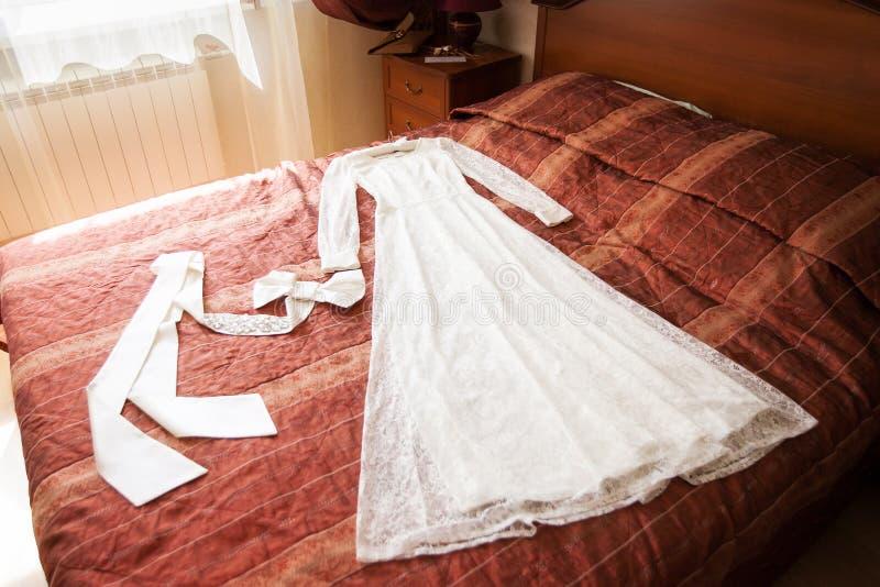 Härlig bröllopsklänning och tillbehör på soffan selektiv fokus royaltyfri bild