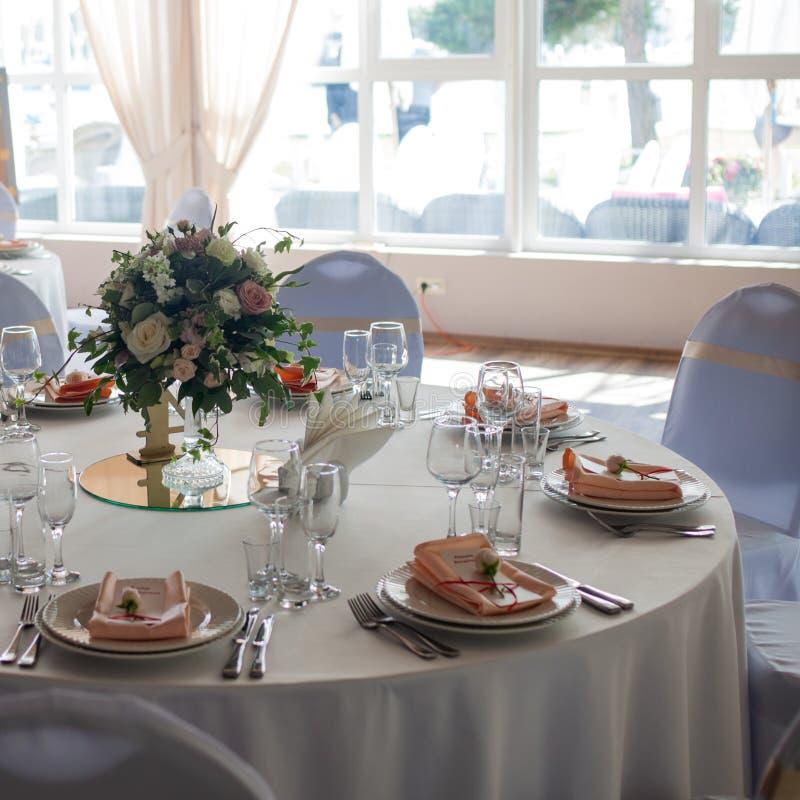 Härlig brölloptabell, rund tabell för gäster, bukett av blommor i mitten arkivfoton