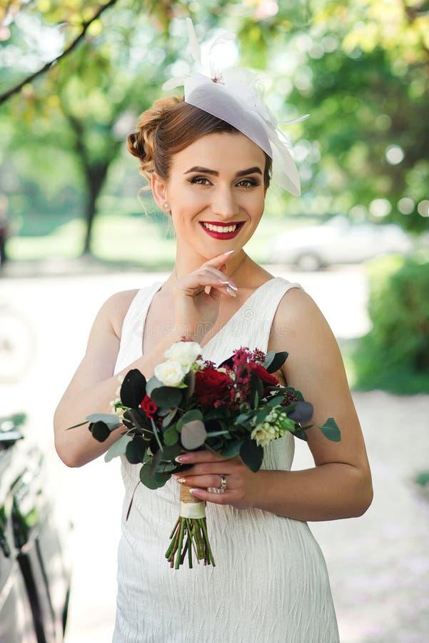 härlig brud Bröllopbukett i händer för brud` s den härliga gulliga frisyren låser model ståendeprofilbröllop Modemodell med perfe arkivfoton