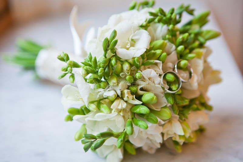 Härlig brud- bukett med vita freesia och vigselringar En stor bakgrundsbild closeup Begrepp av den lyckliga gifta sig dagen royaltyfri foto