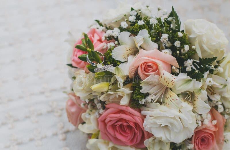 Härlig brud- bukett, vita guld- vigselringar på blommor royaltyfria foton