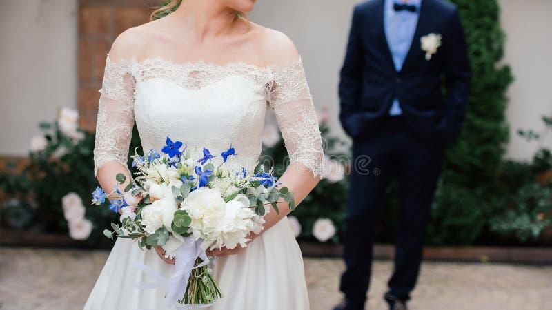 Härlig brud i bröllopsklänning med att gifta sig buketten av pioner arkivbilder