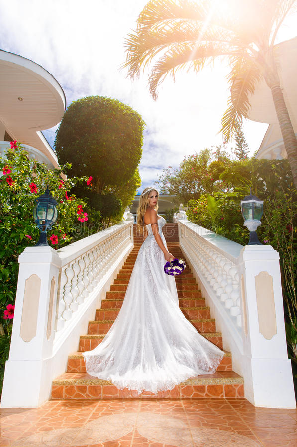 Härlig brud i bröllopsklänning med långt drevanseende på royaltyfria foton