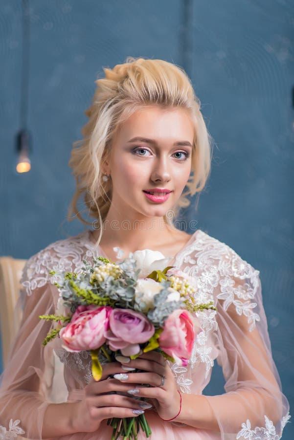 Härlig brud i bröllopsklänningen som poserar med buketten i händer royaltyfri bild