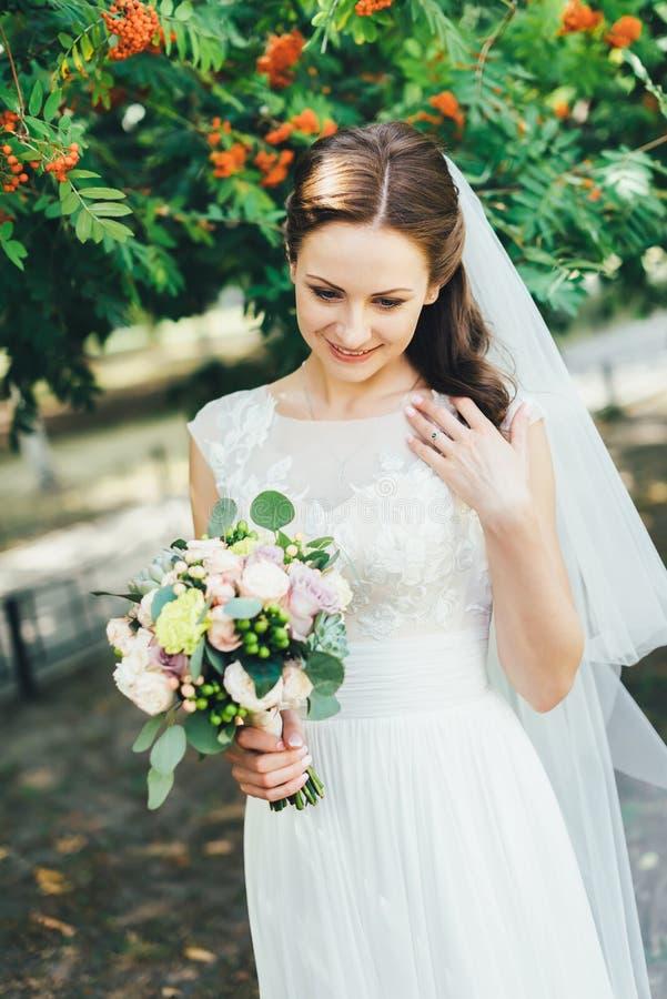 Härlig brud i den vita bröllopsklänningen utomhus arkivbilder
