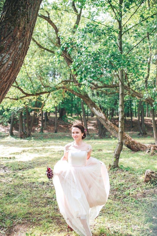 Härlig brud i den vita klänningen för tappning som går i parkera Ursnygg stilfull brud arkivfoton