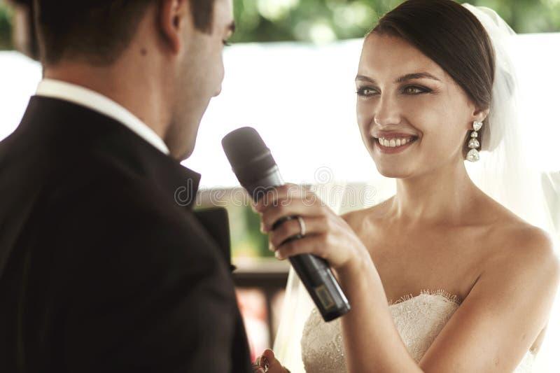Härlig brud i den vita klänningen och stiliga brudgummen som utbyter rin royaltyfria foton