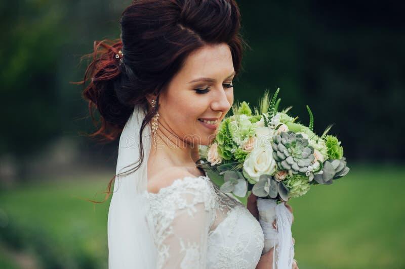 Härlig brud i elegant vit bröllopsklänning med vit bouque royaltyfria bilder
