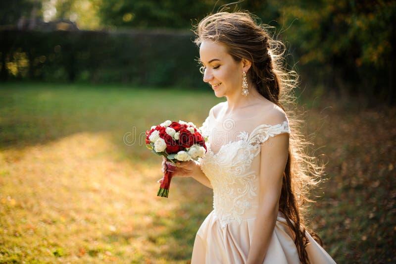 Härlig brud i en vit bröllopsklänning som rymmer en beauriful bukett för röda rosor arkivbilder