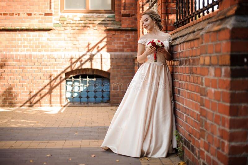 Härlig brud i ett vitt bröllopsklänninganseende nära väggen för röd tegelsten arkivfoton