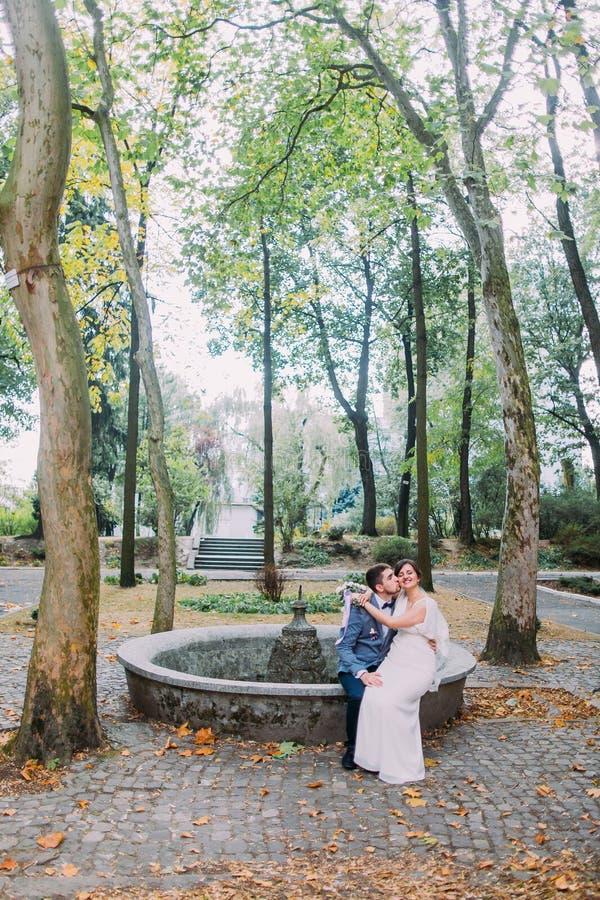 Härlig brud i siden- sammanträde för bröllopkappa på knä av henne som älskar brudgummen Charmiga torkade nygift personpar vilar v arkivbild