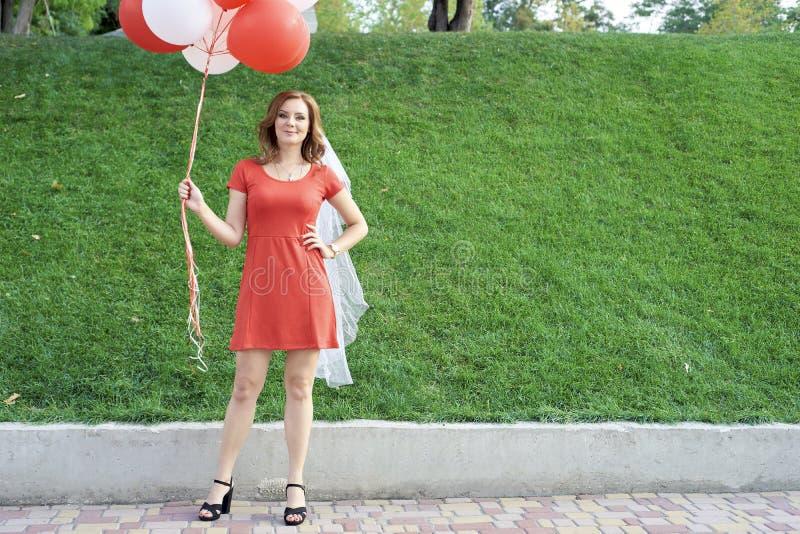 Härlig brud med ballonger i parkera royaltyfri foto
