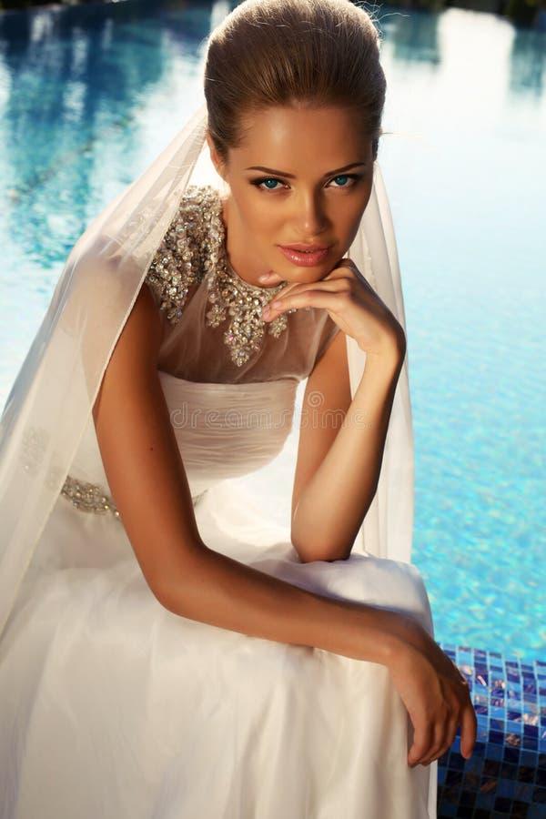 Härlig brud med blont hår i elegant bröllopsklänning royaltyfri fotografi