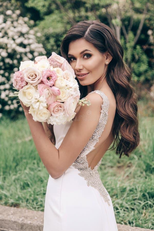 Härlig brud med mörkt hår i lyxig bröllopsklänning med den mjuka bröllopbuketten royaltyfria foton