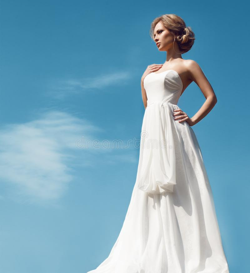 Härlig brud med modebröllopfrisyren - på himmelbakgrund arkivbilder