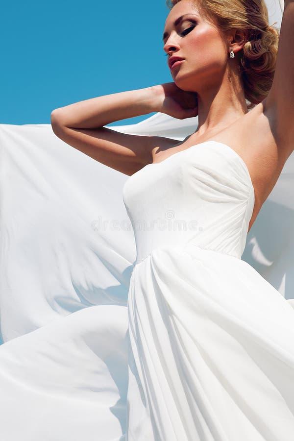 Härlig brud med modebröllopfrisyren - på himmelbakgrund arkivfoto