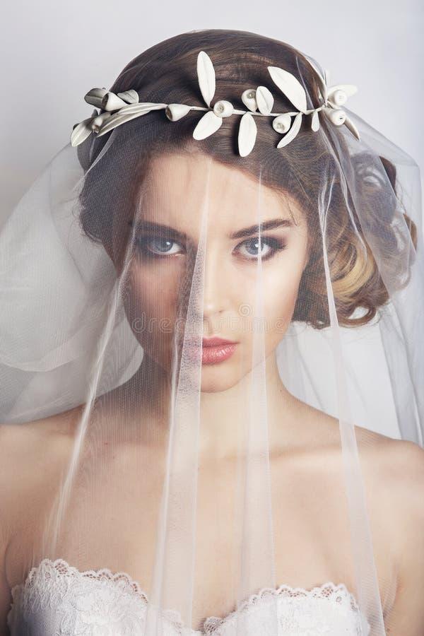Härlig brud med modebröllopfrisyren - på vit bakgrund Closeupstående av den unga ursnygga bruden fotografering för bildbyråer