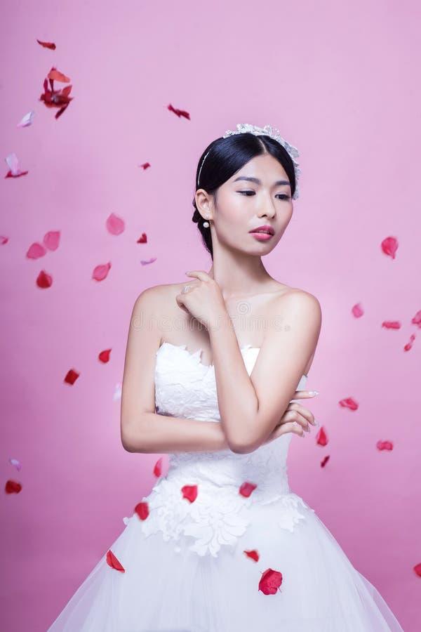 Download Härlig Brud Med Rosa Kronblad I Mitt--luft Anseende Mot Rosa Bakgrund Arkivfoto - Bild av blomma, hår: 78731850