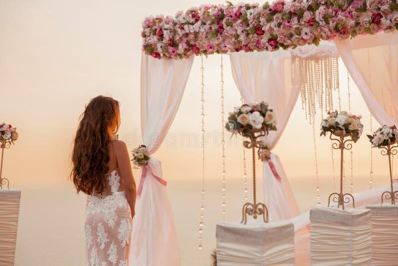 Härlig brud på ceremoni, brunettanseende, genom att gifta sig båge w royaltyfria bilder