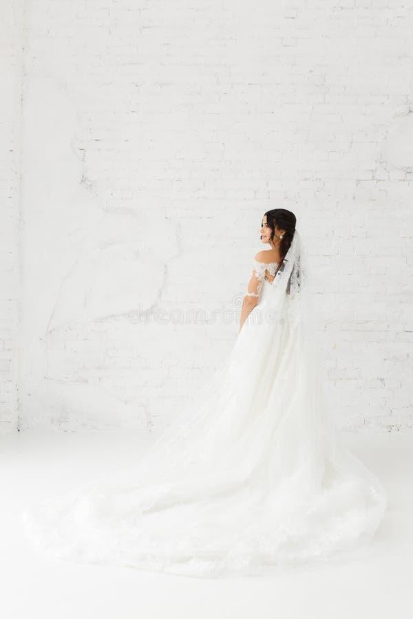 Härlig brud på vit bakgrund för tegelstenvägg Full-lenght stående royaltyfri foto