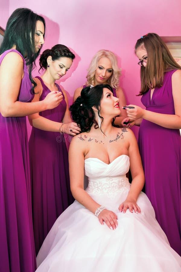 Härlig brud samman med 4 brudtärnor i violetta liknande klänningar royaltyfri bild
