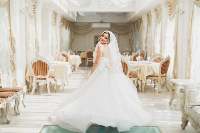 Härlig brud som poserar i bröllopsklänning i modehotell arkivfoton