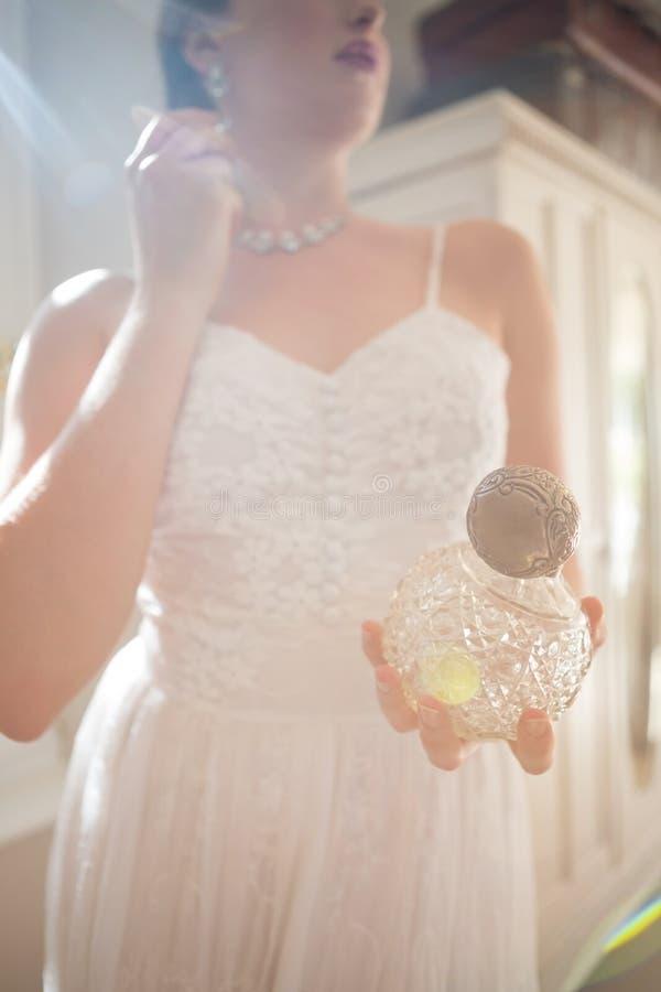 Härlig brudinnehavdoft, medan bära örhänget hemma fotografering för bildbyråer