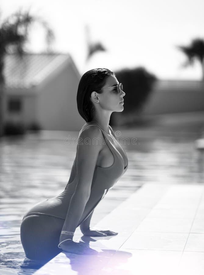 Härlig brunbränd kvinna i blå swimwear som kopplar av i simbassängbrunnsort nära den dyra villan på varm sommardag arkivbilder