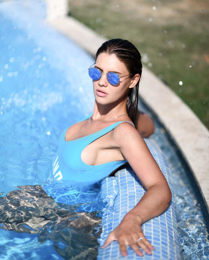 Härlig brunbränd kvinna i blå swimwear som kopplar av i simbassängbrunnsort nära den dyra villan på varm sommardag arkivfoto
