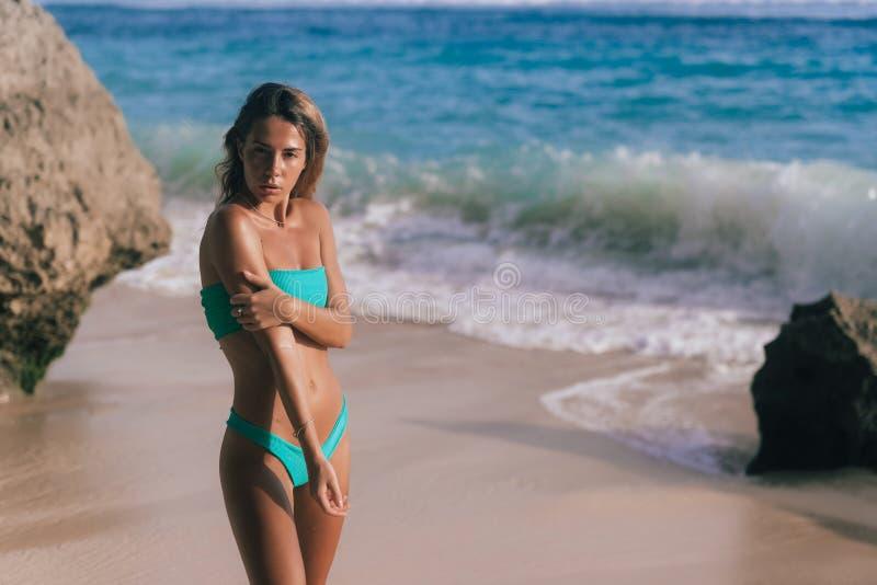 Härlig brunbränd kvinna i den separata baddräkten som poserar på stranden och ser in mot havet royaltyfria bilder
